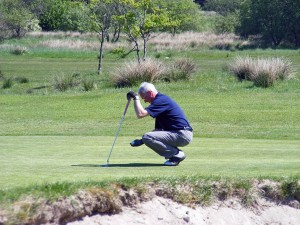 man teeing up golf shot